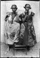 Seidou Keïta, Senza Titolo, 1952-55. Seidou Keïta, C.A.A.C. - The Pigozzi Collection, Ginevra [la foto rappresenta due amiche con stesse acconciature ed oggetti ornamentali tradizionali]