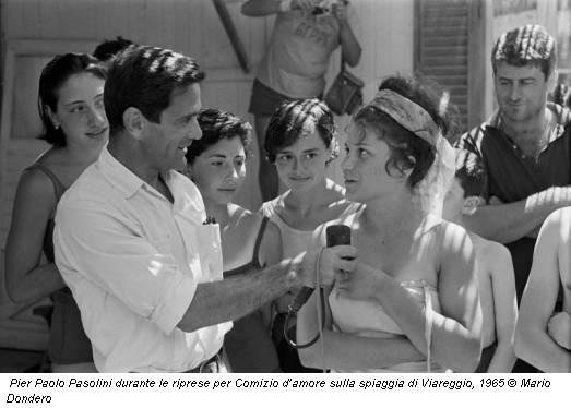 Pier Paolo Pasolini durante le riprese per Comizio d'amore sulla spiaggia di Viareggio, 1965 © Mario Dondero