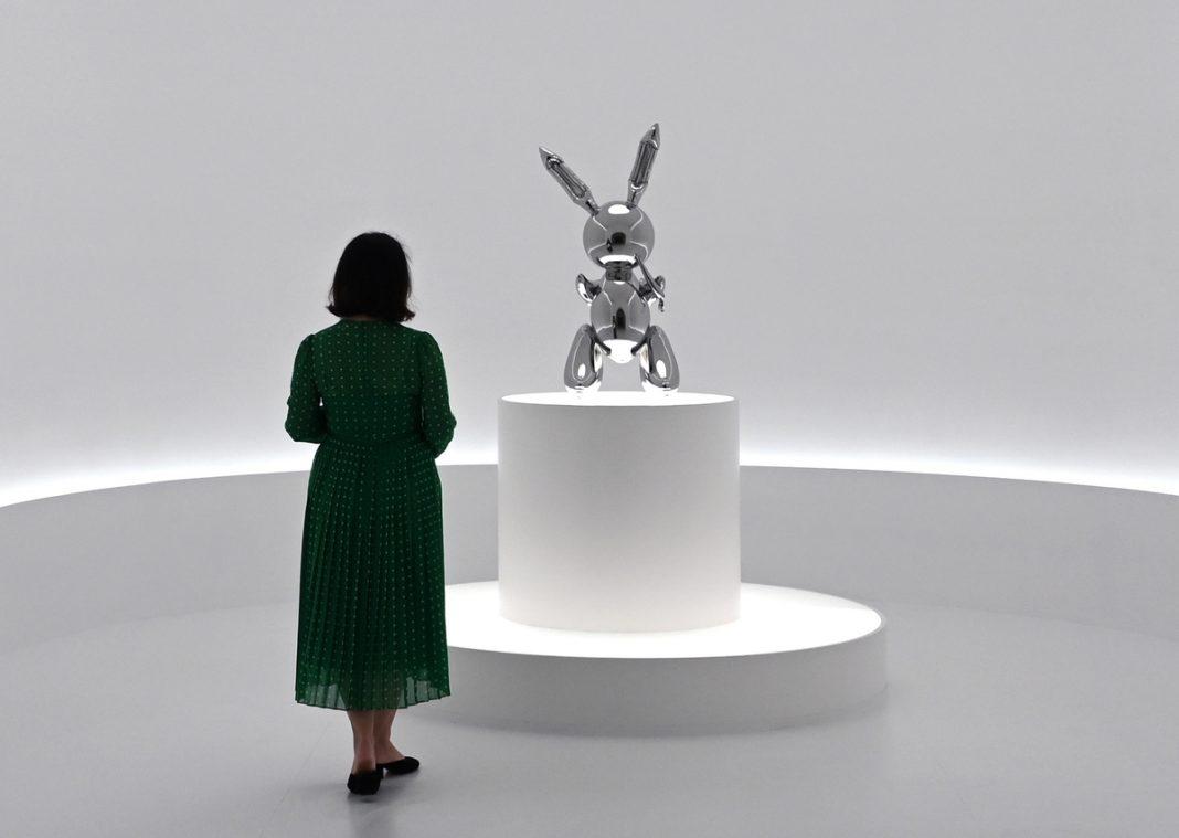 "A woman looks at Jeff Koons' ""Rabbit"