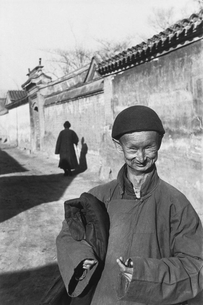 Près de la Cité interdite, un simple d'esprit dont la fonction est d'accompagner les mariées en palanquin, Pékin, décembre 1948. © Fondation Henri Cartier-Bresson / Magnum Photos