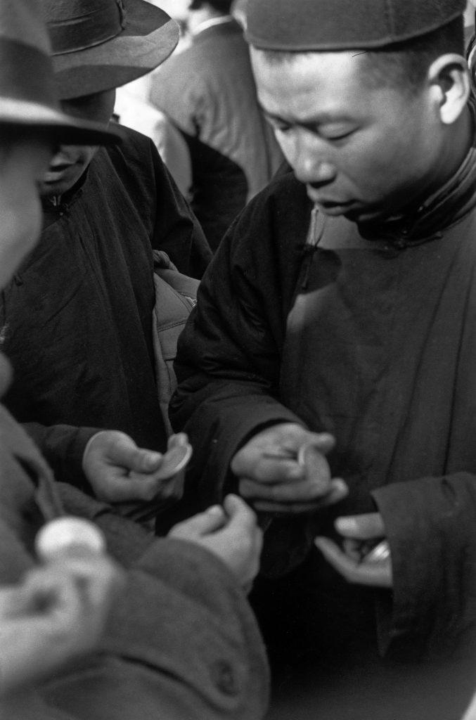 Scène du marché noir des pièces d'argent, Pékin, décembre 1948. © Fondation Henri Cartier-Bresson / Magnum Photos