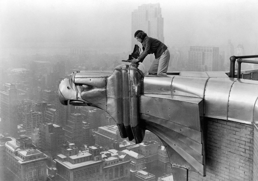 Margaret Bourke-White, a photographer for LIFE magazine, makes a precarious photo from one of the eagles on the 61st floor of the Chrysler Building in New York City in 1934