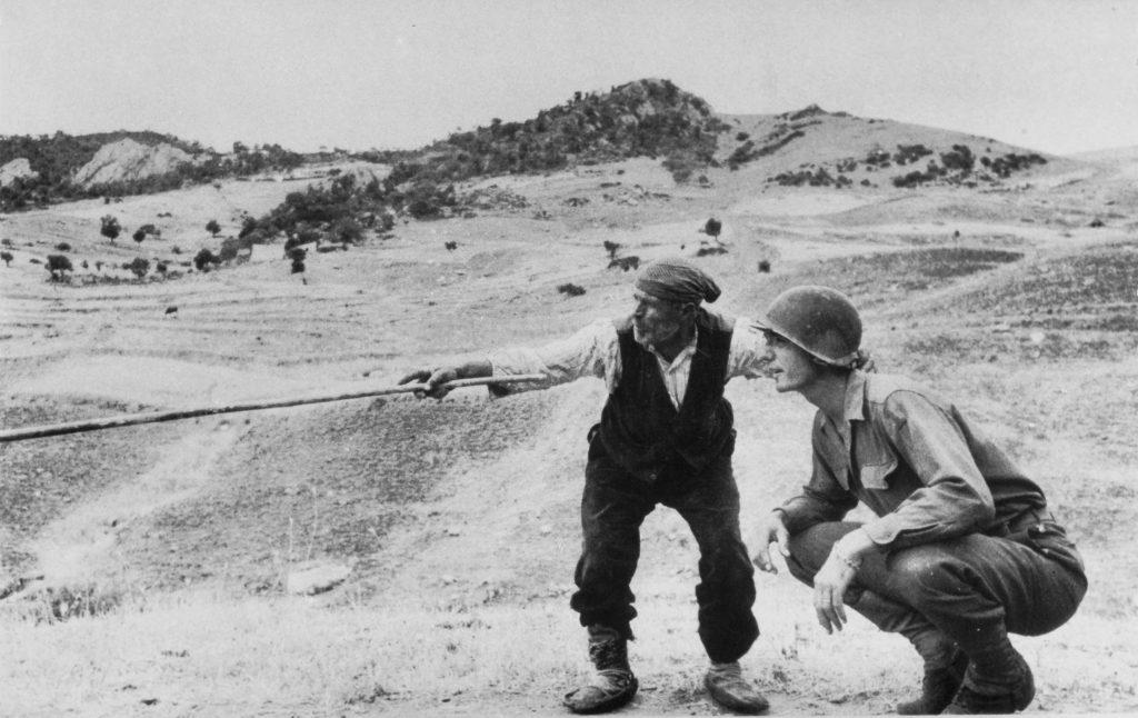 Robert Capa, Sicilia, nei pressi di Troina (provincia di Enna), agosto 1943. Contadino siciliano indica a ufficiale statunitense la strada presa dai tedeschi. 1943 © Robert Capa Courtesy International Center of Photography/Magnum Photos/contrasto