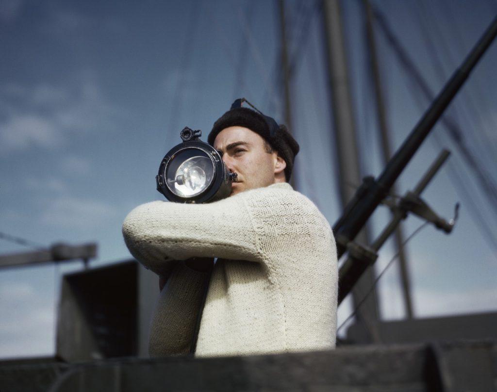 Robert Capa. Un membro dell'equipaggio segnala a un'altra nave di un convoglio alleato che attraversa l'Atlantico, 1942. Credits: Robert Capa International Center of Photography/Magnum Photos
