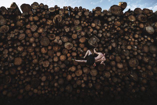 """Sport, 1° premio Log Pile Bouldering © Adam Pretty, Australia, Getty Images Un uomo si arrampica su una catasta di tronchi mentre si allena per il """"boulder"""" – l'arrampicata su piccole formazioni rocciose e massi di solito non più alti di sei metri, senza corde o imbracature – a Kochel am See, Baviera, Germania, il 15 settembre."""