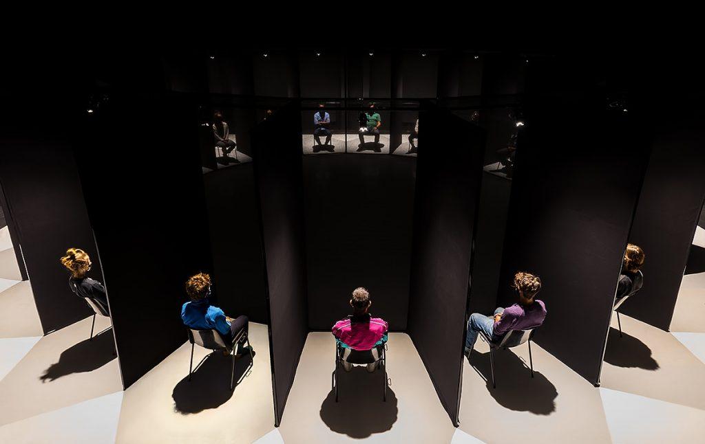 Panopticon con i visitatori-spettatori nelle postazioni singole separate da pannelli neri. Foto Serena Nicoletti